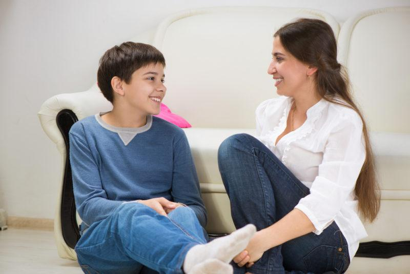 mom and teen son talking on the couch