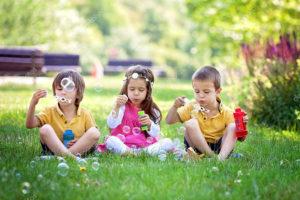 three kids blowing bubbles
